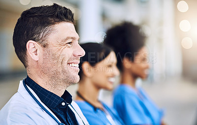 Buy stock photo Defocused shot of a group of medical practitioners standing together