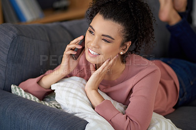 Buy stock photo Cropped shot of an attractive young woman making a phonecall while relaxing on her sofa at home
