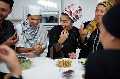 Buy stock photo Shot of a group of young muslim friends enjoying fruits and treats together in the kitchen indoors