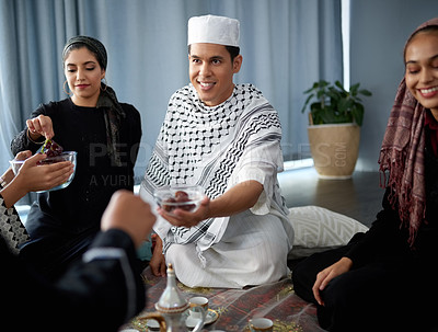 Buy stock photo Shot of a group of young muslim friends sharing bowls of fruit at a gathering indoors