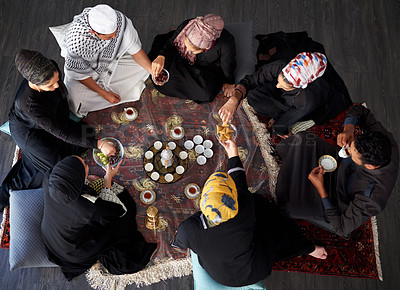 Buy stock photo High angle shot of a group of young muslim friends having tea and treats at a gathering indoors