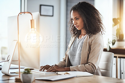 Buy stock photo Shot of a young businesswoman working on her computer