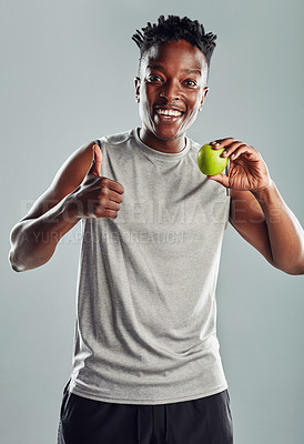 Buy stock photo Shot of a sporty young man holding an apple against a grey background
