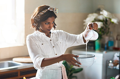 Buy stock photo Cropped shot of a cheerful young woman baking inside of her home during the day