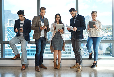 Buy stock photo Full length shot of a diverse group of businesspeople using wireless technology in an office