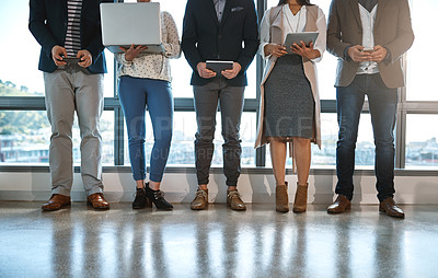 Buy stock photo Shot of an unrecognizable group of businesspeople using wireless technology in an office