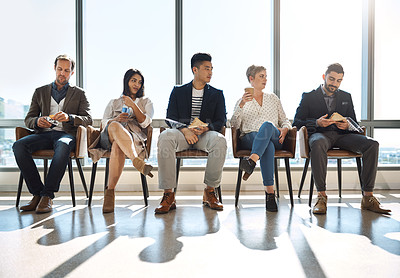 Buy stock photo Shot of a group of businesspeople taking a break while sitting in line in an office