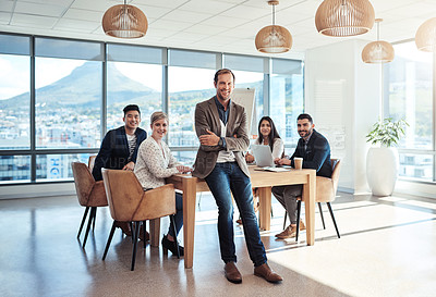 Buy stock photo Portrait of a mature businessman standing in an office with his colleagues in the background