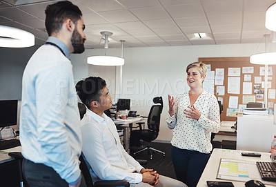 Buy stock photo Cropped shot of an attractive young female creative chatting to her colleagues while working in the office