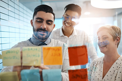 Buy stock photo Cropped shot of three young businesspeople brainstorming with sticky notes on a glass wall in the office
