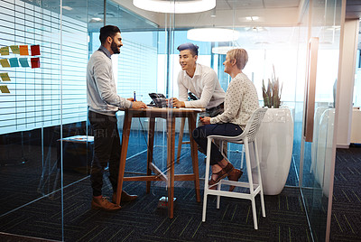 Buy stock photo Full length shot of three young businesspeople having a meeting in their office