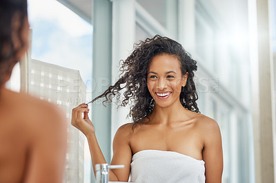 Buy stock photo Shot of an attractive young woman doing her hair during her morning beauty routine at home