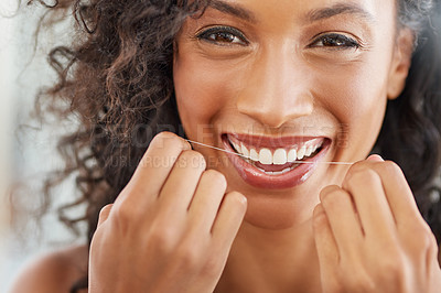 Buy stock photo Portrait of an attractive young woman flossing her teeth in the bathroom at home