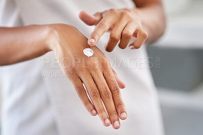 Buy stock photo Cropped shot of a woman applying moisturiser to her hands during her morning beauty routine