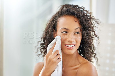 Buy stock photo Shot of an attractive young woman wiping her face with a towel during her morning beauty routine