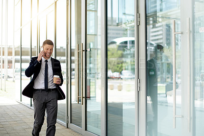 Buy stock photo Shot of a handsome businessman taking a phone call while walking outside an office building