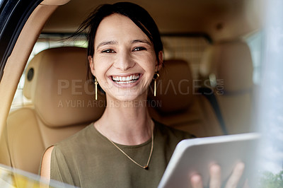 Buy stock photo Portrait of a beautiful young businesswoman using a digital tablet while sitting in the backseat of a car