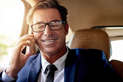 Buy stock photo Portrait of a mature businessman making a phone call while sitting in the backseat of a car
