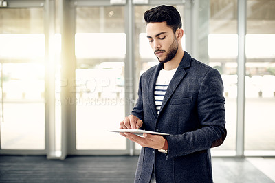 Buy stock photo Cropped shot of a handsome young businessman using a tablet while standing in his office