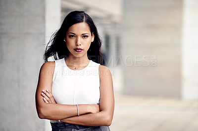 Buy stock photo Cropped portrait of an attractive young businesswoman standing with her arms folded outside
