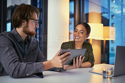 Buy stock photo Shot of a young businesswoman and businessman using a digital tablet during a late night meeting at work