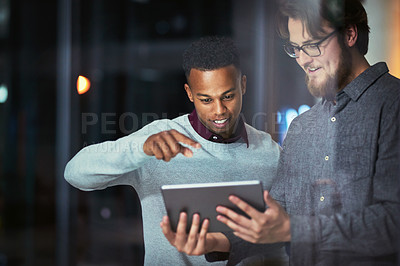 Buy stock photo Shot of two young businessmen using a digital tablet together during a late night at work