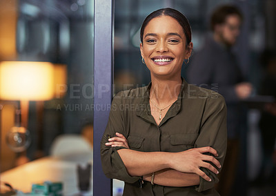 Buy stock photo Portrait of a confident young businesswoman working late at night in a modern office