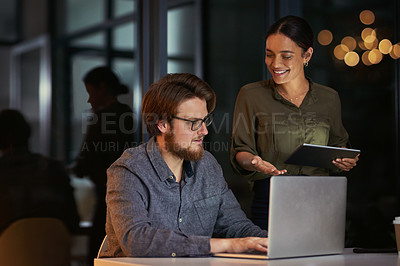 Buy stock photo Shot of a young businessman and businesswoman using a laptop together during a late night at work