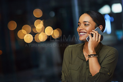Buy stock photo Cropped shot of a cheerful young businesswoman talking on her cellphone inside the office during the night