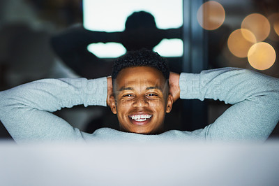 Buy stock photo Cropped shot of a cheerful young businessman working on a computer and relaxing  in the office at night