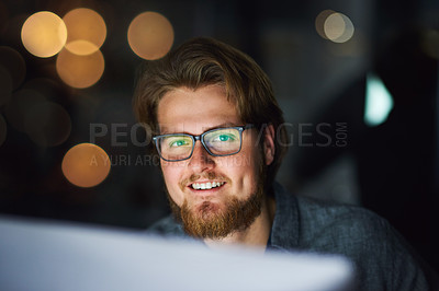 Buy stock photo Portrait of a cheerful young businessman working on a computer in the office at night