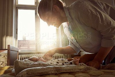 Buy stock photo Cropped shot of an unrecognizable young mother bonding with her baby on a bed at home