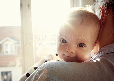 Buy stock photo Cropped shot of an adorable baby being cuddled by her mother at home