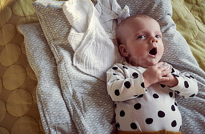 Buy stock photo High angle shot of a baby yawning while lying down on a bed at home