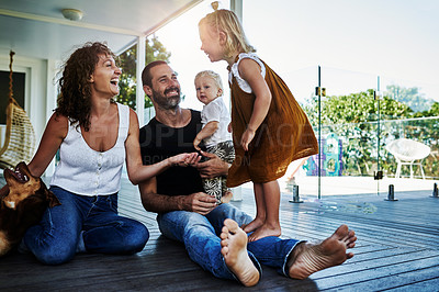 Buy stock photo Full length shot of two loving parents being playful with their kids on their veranda at home