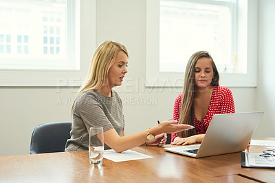 Buy stock photo Shot of two young businesswomen working on a laptop together in an office