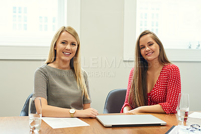 Buy stock photo Portrait of two beautiful young businesswomen working together in an office