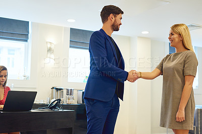 Buy stock photo Shot of two young businesspeople shaking hands in an office
