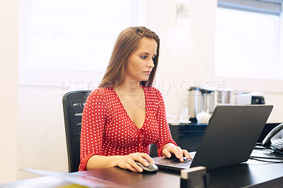 Buy stock photo Shot of a beautiful young businesswoman working on a laptop at her office desk