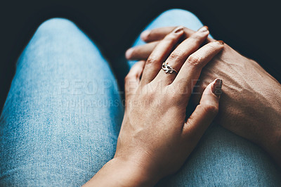 Buy stock photo Closeup shot of an unrecognizable couple holding hands while sitting indoors