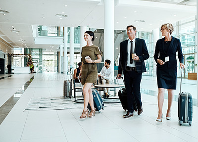 Buy stock photo Shot of three confident businesspeople walking with their luggage inside of a airport during the day