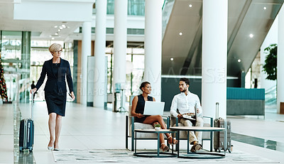 Buy stock photo Shot of a confident mature businesswoman walking with her luggage inside of a airport during the day