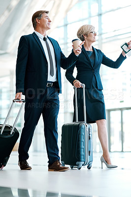 Buy stock photo Shot of two confident businesspeople walking with their luggage inside of a airport during the day