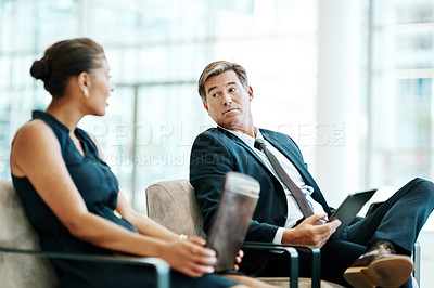 Buy stock photo Shot of two confident businesspeople seated on chairs while waiting for their flights inside of an airport