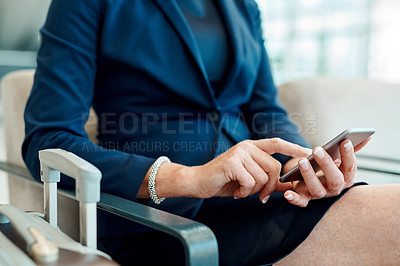 Buy stock photo Shot of an unrecognizable businesswoman seated with her luggage while browsing on a digital tablet inside of a airport during the day
