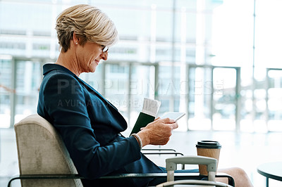 Buy stock photo Shot of a confident mature businesswoman seated with her luggage while browsing on a cellphone inside of a airport during the day