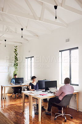 Buy stock photo Shot of a group of young businesspeople using computers at their desks in a modern office