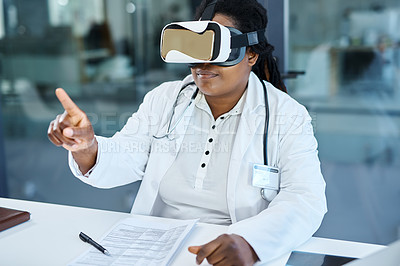 Buy stock photo Shot of a female doctor wearing a VR headset while working in her office