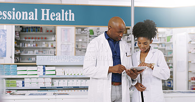 Buy stock photo Cropped shot of two pharmacists using a digital tablet  while having a discussion in a chemist