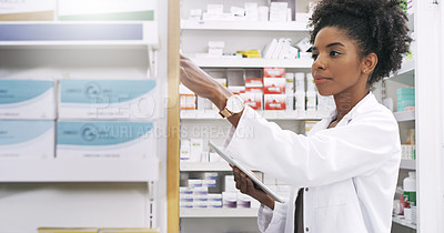 Buy stock photo Cropped shot of an attractive young pharmacist taking out a product from the shelves while holding a digital tablet